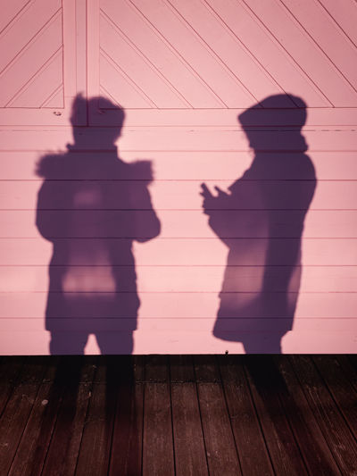 Silhouette shadow of a boy and a girl using a smartphone on a pink wooden background.