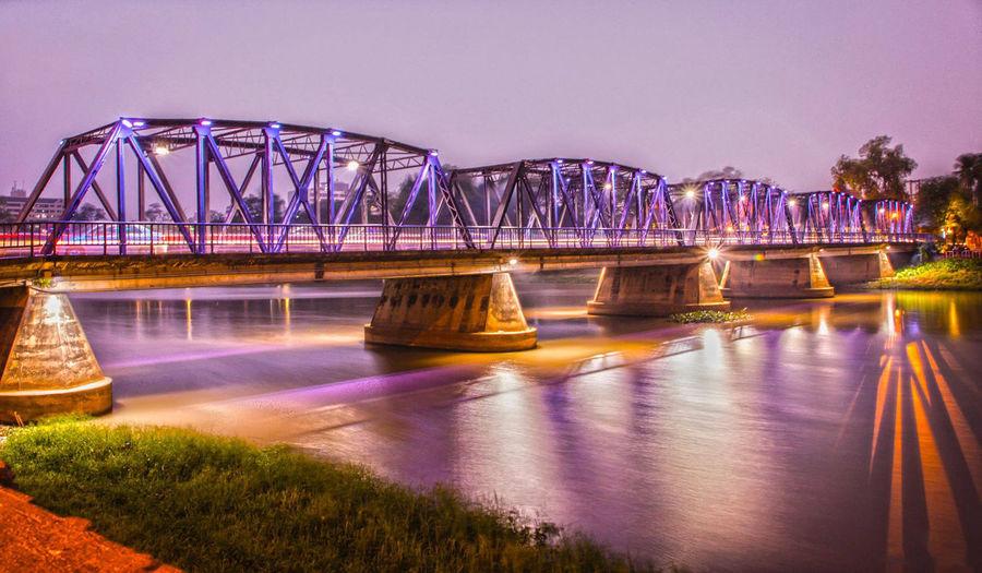 Illuminated bridge over river against sky at dusk
