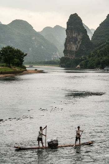 Men on wooden raft sailing in river