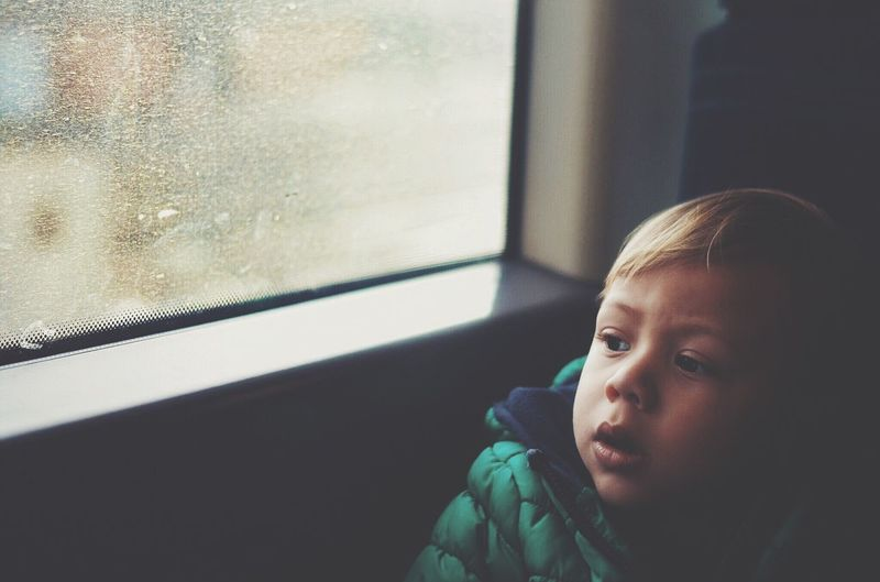 High Angle View Of Boy Looking Through Train Window