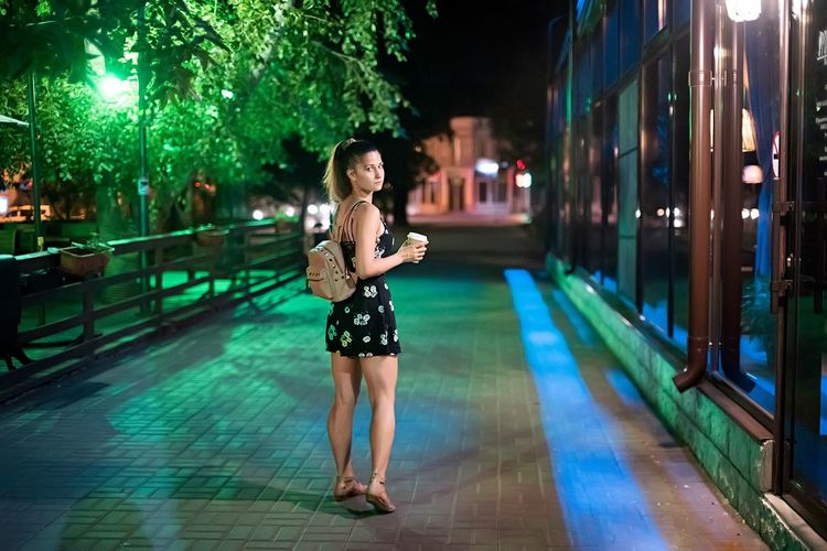 Full length of woman on street in city at night
