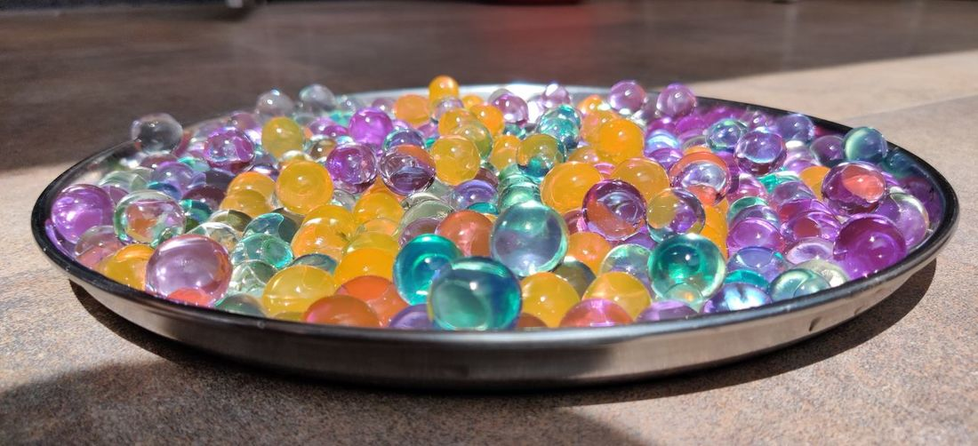 High angle view of multi colored candies in bowl on table
