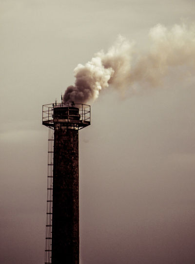 Air Pollution Architecture Building Exterior Built Structure Chimney Day Emitting Environment Environmental Issues Factory Fumes Industry Low Angle View No People Outdoors Pollution Sky Smoke - Physical Structure Smoke Stack
