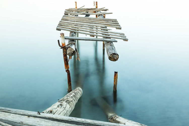 Abandoned wooden pier over lake