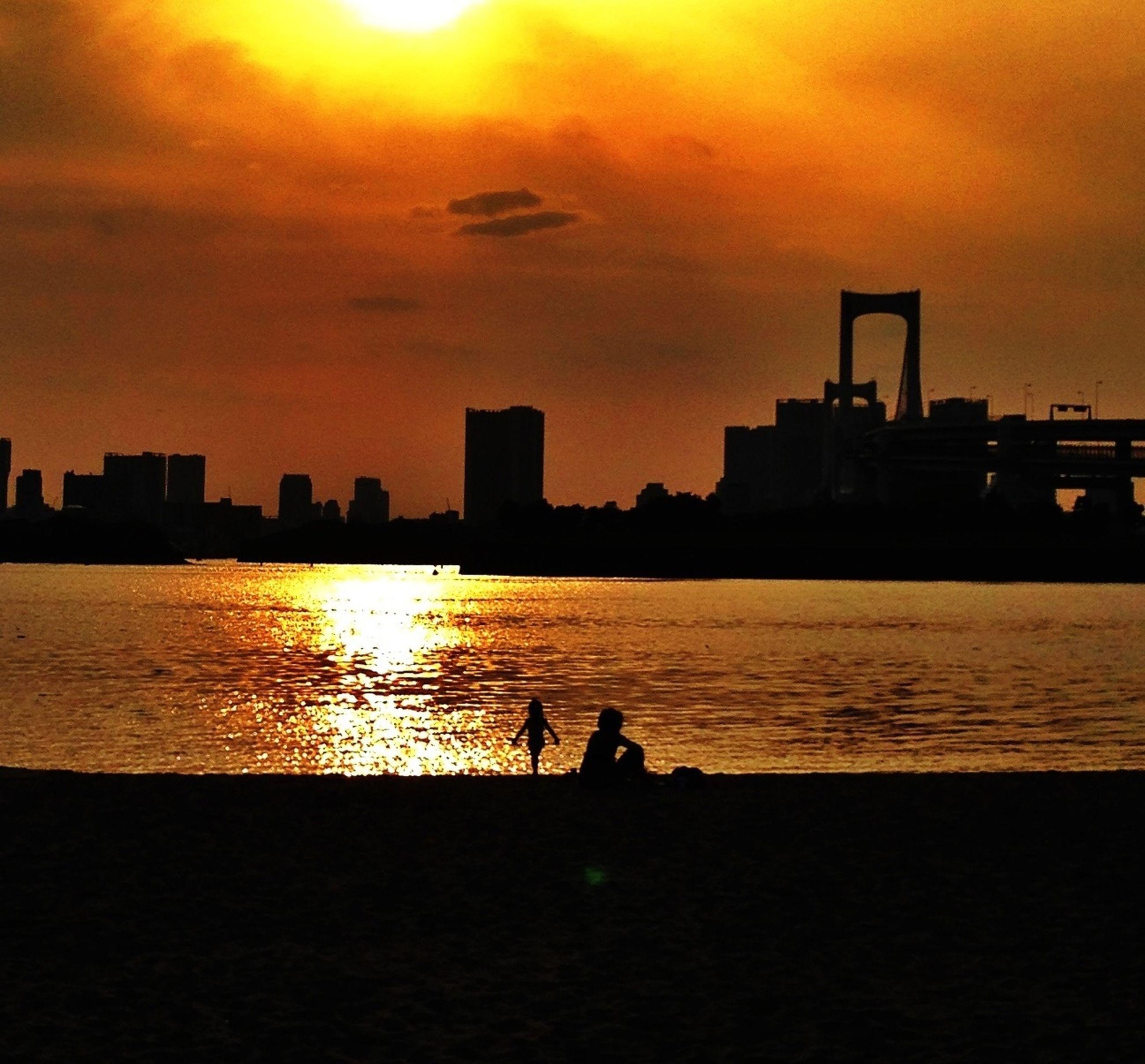 sunset, silhouette, water, orange color, sky, architecture, built structure, building exterior, men, sun, city, reflection, lifestyles, river, leisure activity, scenics, sea, beauty in nature, nature