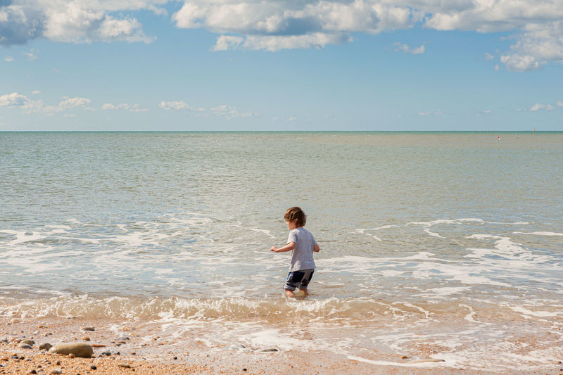 Cute boy standing on shore against sky