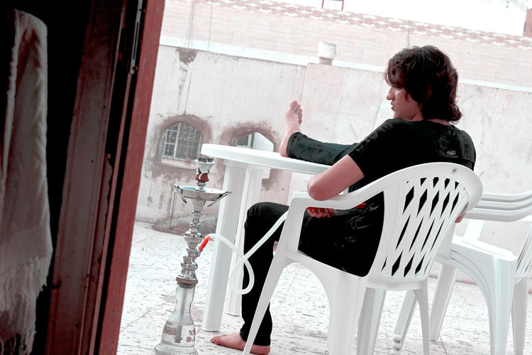 Man Smoking Hookah While Sitting On Chair In Balcony