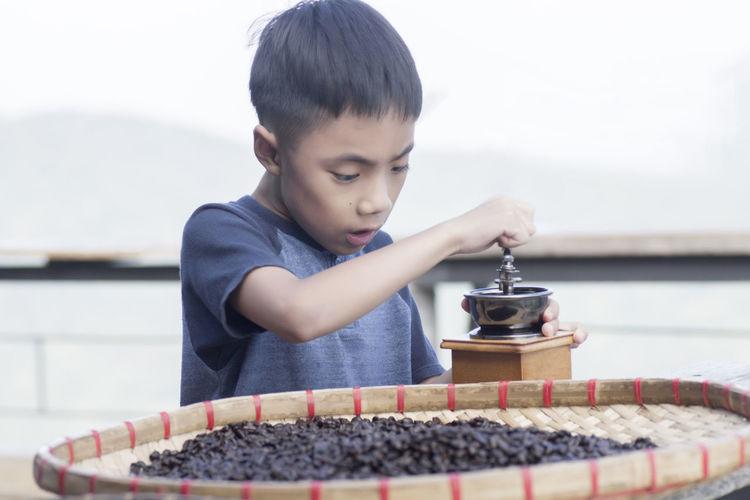 Boy grending coffee beans