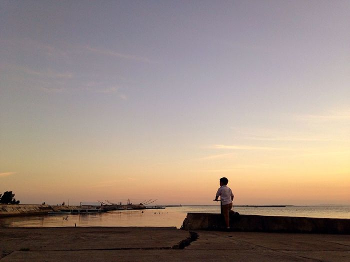Rear view of boy standing on pier against sky during sunset