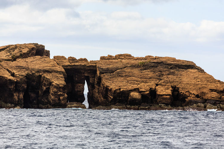 Rock formations by sea against sky