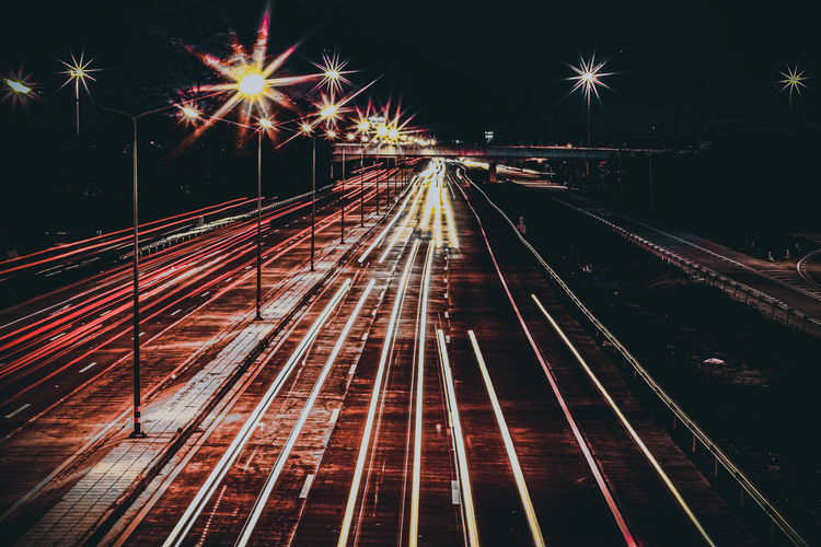High angle view of light trails on railroad tracks at night