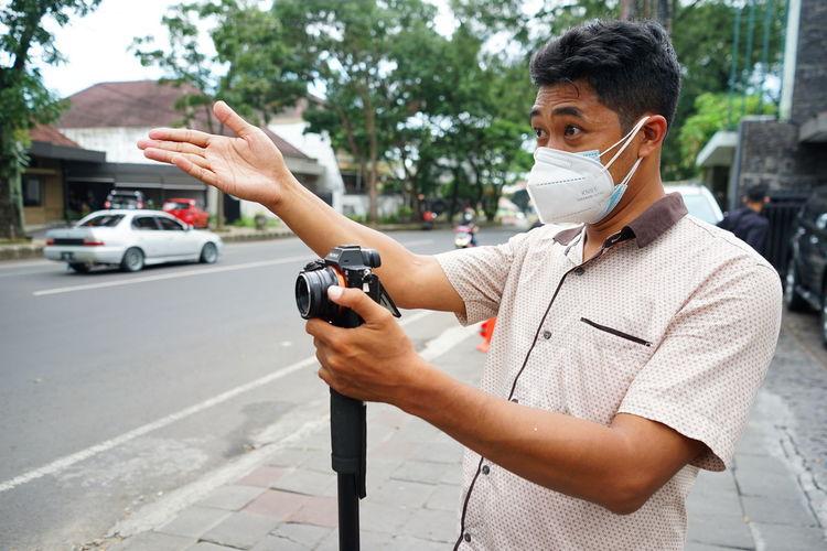 A cameraman wearing a mask directed tallent