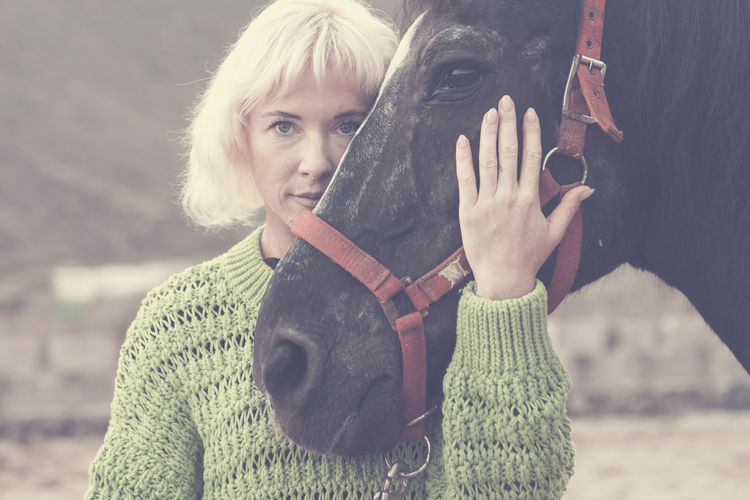 blonde beautiful caucasian model woman with black amazing horse stay together in friendship in fashion style picture concept outdoor nature - hug with love for friends human and animal Warm Clothing Winter Clothing Focus On Foreground Portrait Real People Front View One Person Adult Sweater Headshot Women Day Holding Leisure Activity Blond Hair Looking At Camera Casual Clothing Scarf Outdoors Hairstyle Horse Bestfriend Love Bonding Affectionate Black Color Sunset Caucasian Relaxing Serene People Cute Fashion Friends Therapy