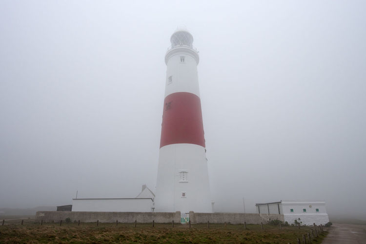 Portman Bill Lighthouse during heavy fog weather conditions on the Isle of Portland, Dorset, England. Portland Bill Architecture Building Building Exterior Built Structure Day Direction Fog Foggy Guidance Lighthouse Low Angle View Nature No People Outdoors Pollution Protection Safety Security Sky Tall - High Tower