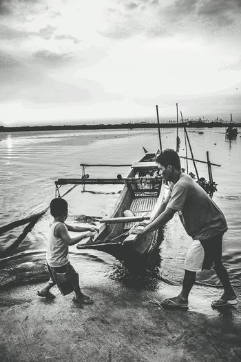 """""""Daddy, Let Me Help You"""" Men Only Men Nautical Vessel Water Outdoors People Adult Fisherman Day Sky Teamwork Rowing Outrigger Father Son Father & Son Fatherhood Moments Kcf Angono, Rizal, Philippines"""