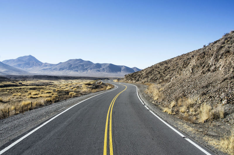 Beauty In Nature Clear Sky Direction Dividing Line Double Yellow Line Landscape Long Mountain Mountain Range Nature No People Outdoors Road Road Marking Scenics - Nature Sky The Way Forward Tranquil Scene Transportation Way