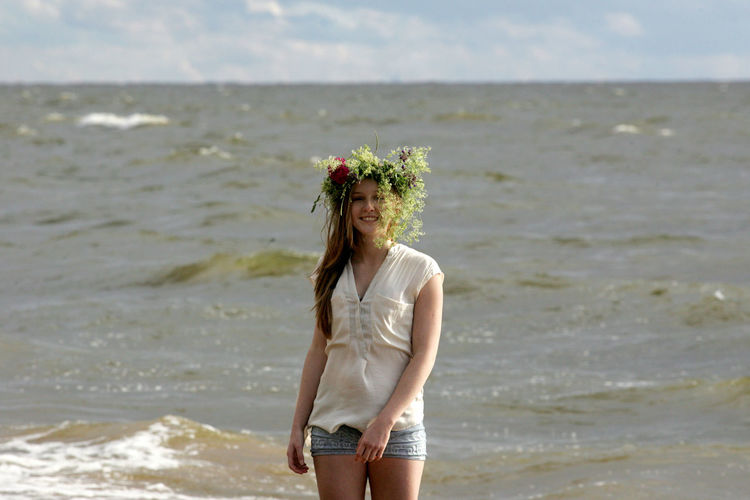 Young woman standing at beach against sky