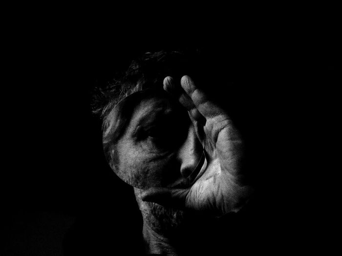Close-up of hand and face against black background