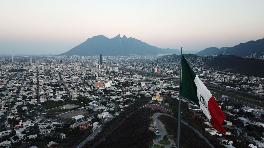 Mexican flag in city against clear sky during sunrise