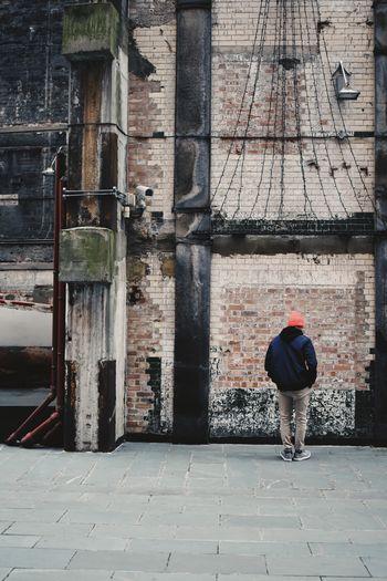 Rear View Of Teenage Boy Standing On Street In City