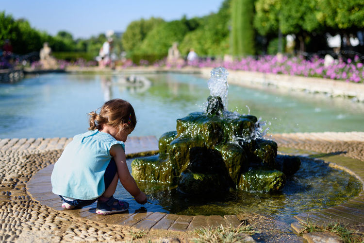 Little child playing at a water fountain in a park on a summer day Children Fountain The Week On EyeEm Child Childhood Children Playing Day First Eyeem Photo Flower Outside Park Playing Summer Water This Is Family