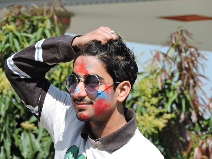 High angle view of young man with powder paint on face wearing sunglasses in park