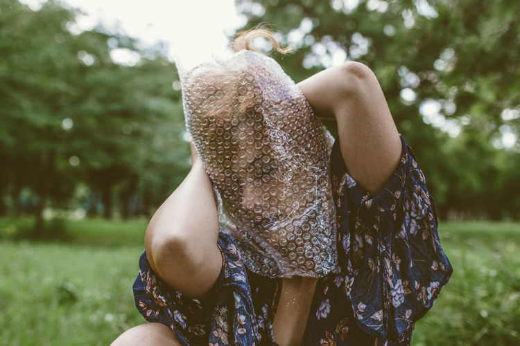 Woman Covering Face With Bubble Wrap Plastic Foil In Park