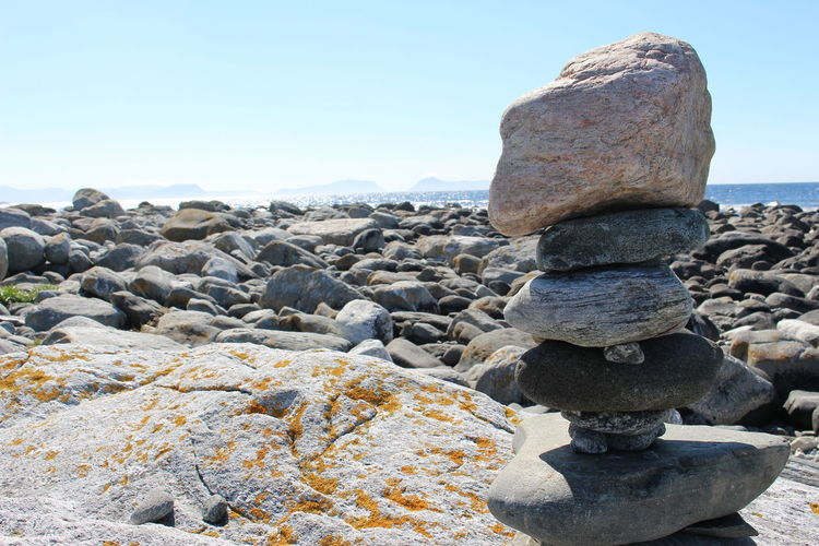 Stack of stones on beach against clear sky