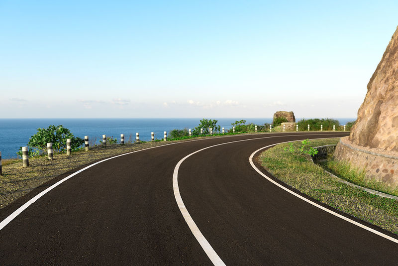 Asphalt coastal road going round cliff edge bend, with blue sea back drop. Bend Curve Road Markings White Lines Windy Road Beauty In Nature Cliff Cliff Edge Coast Road Coastal Road Day Freeway Highway Nature No People Outdoors Road Scenics Sky The Way Forward Windy