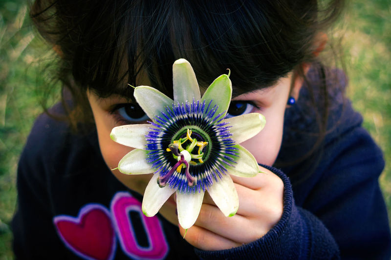 Close-up portrait of girl holding passion flower