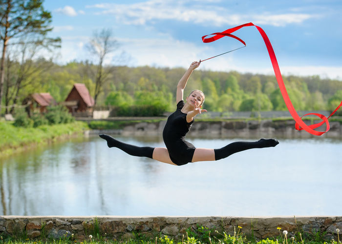 Full Length Portrait Of Woman Gymnast Jumping In Air While Holding Ribbon Against Lake