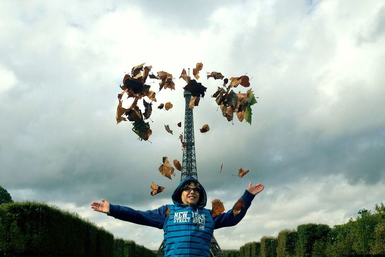 Low Angle View Of Boy Throwing Leaves While Standing Against Eiffel Tower