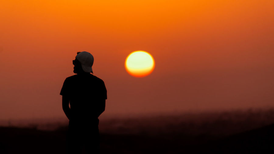 Silhouette man standing on land against orange sky