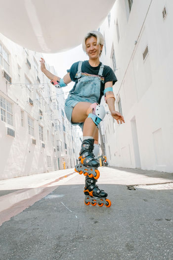 Holidays, sportive activities and hobby concept. young woman with roller skates riding outdoors.