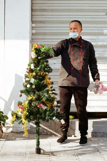 Full length of man standing at christmas tree