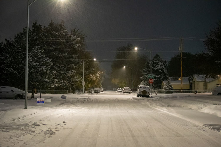 View of snow covered street at night