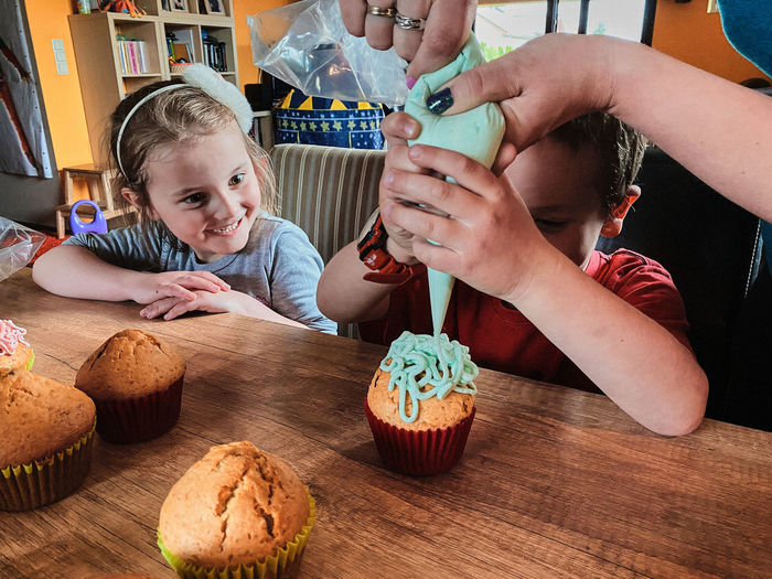 Group of children baking cupcakes, squeezing cream from confectionery bag, preparing ingredients