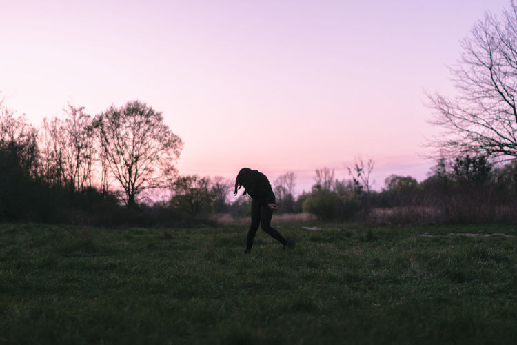 Silhouette person on field against sky during sunset