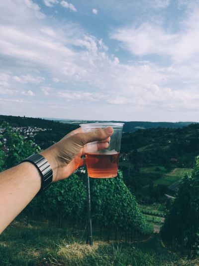 Cropped image of man holding drink against sky
