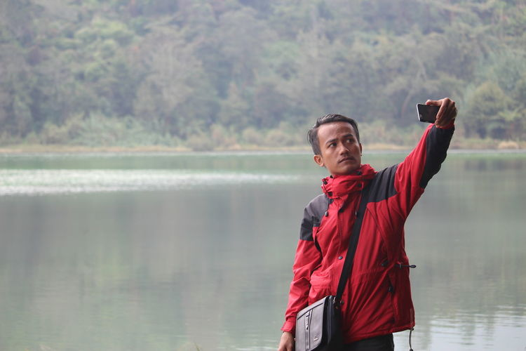 #itsme #hunting #danau #canon700D Beauty In Nature Day Focus On Foreground Lake Leisure Activity Lifestyles Nature One Person Outdoors Real People Red Standing Tree Water Young Adult
