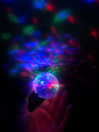 Disco Light holding in the Hand. Human Hand Hand Human Body Part Multi Colored Sphere One Person Holding Nightlife Close-up Illuminated Unrecognizable Person Body Part Reflection Finger Night Nightclub Bubble Indoors  Human Finger Disco Ball