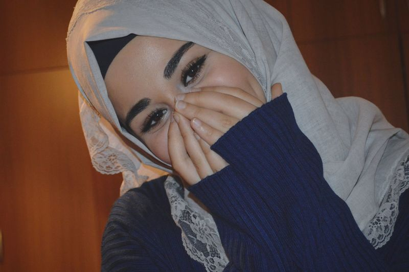 Close-up portrait of young woman in hijab hiding face with hands