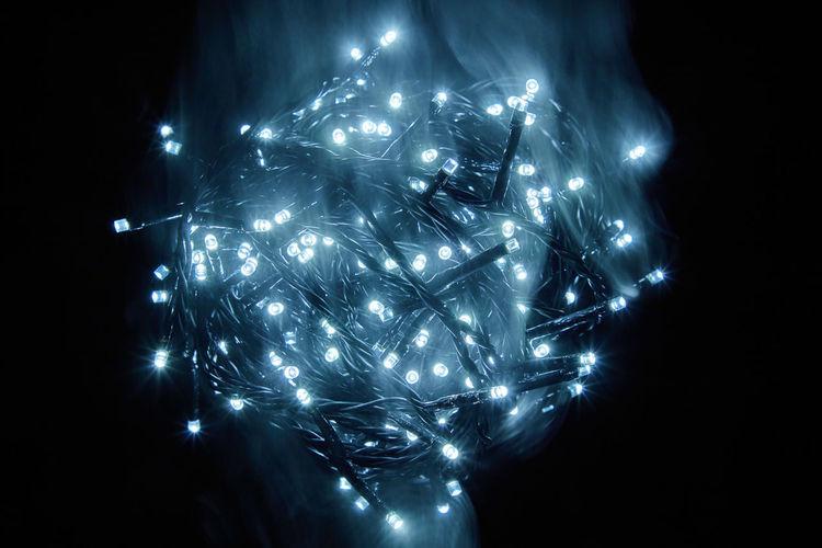 Close-up of illuminated lighting equipment against black background