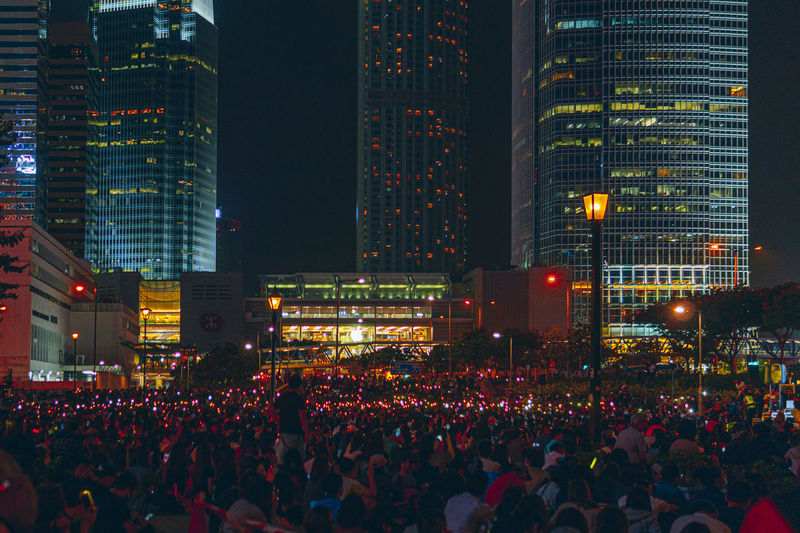 Crowd of people by illuminated building at night