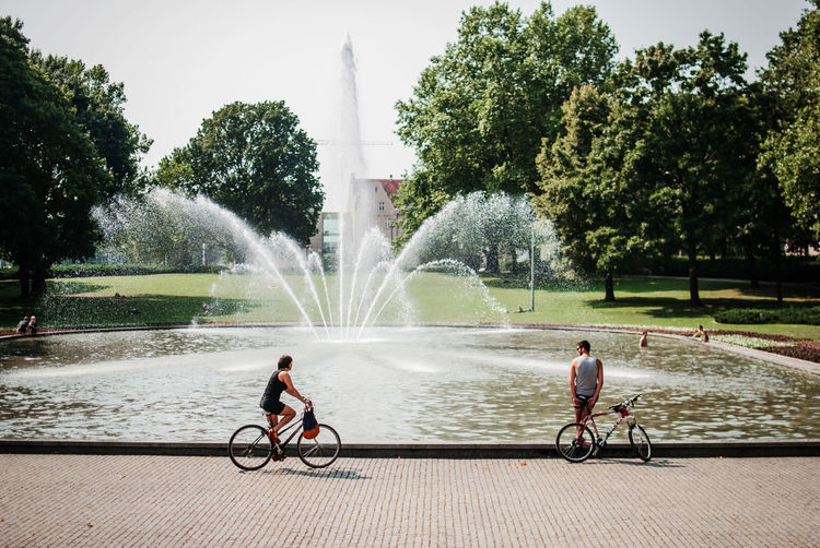 Woman Cycling While Man Leaning On Bicycle By Fountain At Park