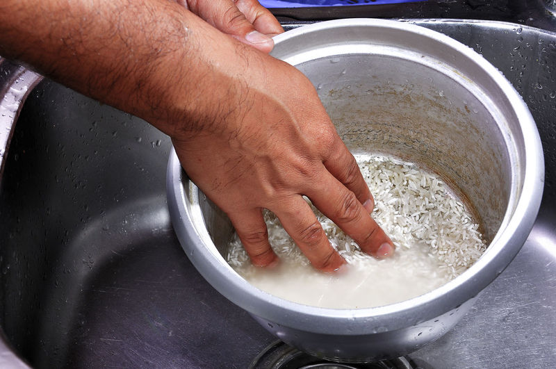 Midsection of woman washing rice in container at sink