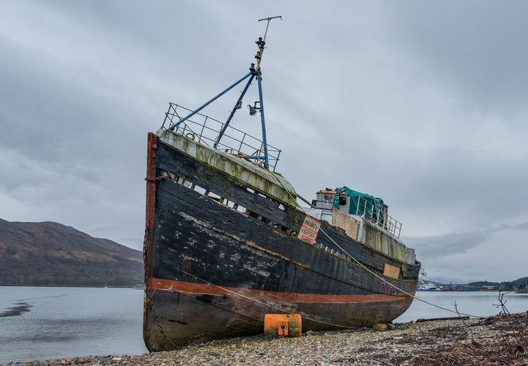Abandoned boat moored at lake