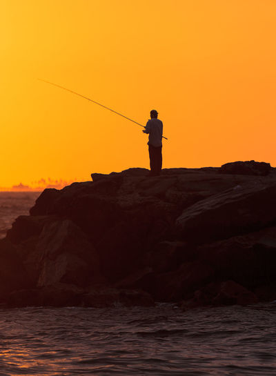 Man fishing while standing on rock by sea against orange sky