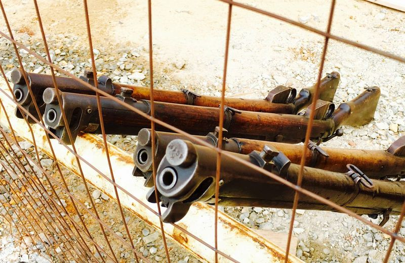 High Angle View Of Guns Seen From Chainlink Fence