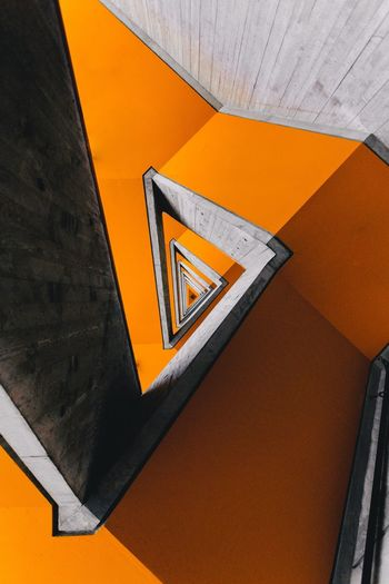 Low angle view of arrow sign on orange wall